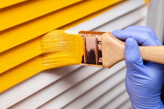 Mano femenina en guante de goma con pincel pintando puerta de madera con pintura amarilla