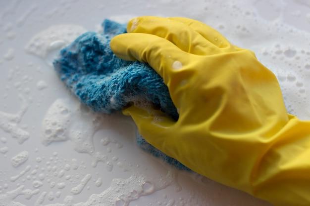 Una mano femenina en un guante lava una superficie con un trapo con espuma. concepto de limpieza de primavera.