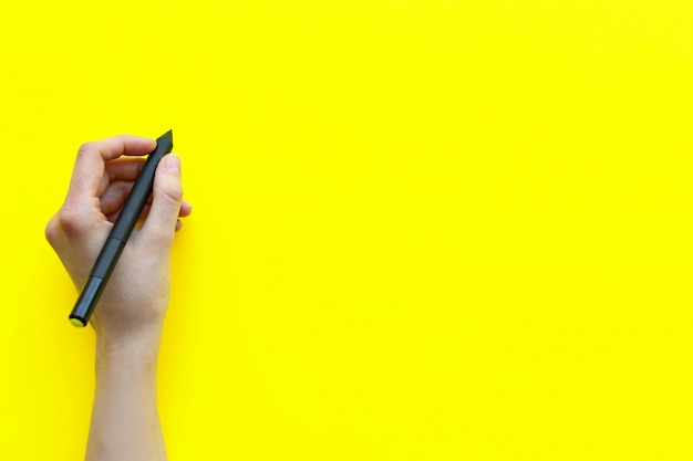 La mano femenina hace un registro en una mesa amarilla monocroma