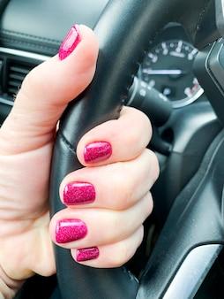 Mano femenina con hermosa manicura en coche