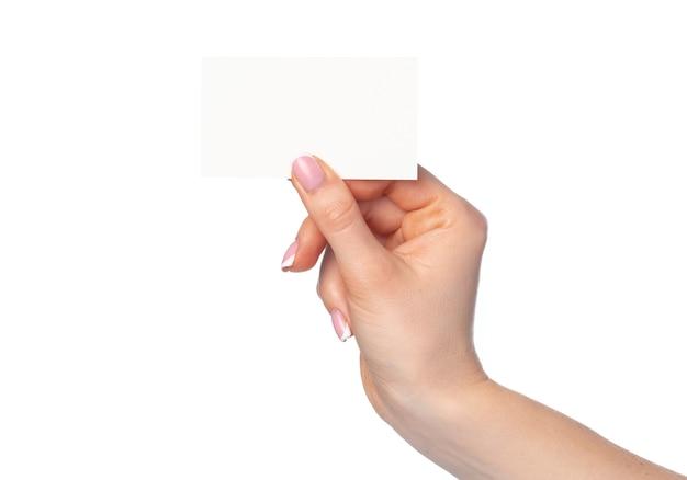 Mano femenina hermosa que sostiene la tarjeta blanca aislada en el fondo blanco
