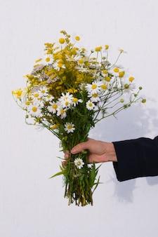 Mano femenina con hermoso ramo de flores amarillas del prado y margaritas sobre fondo claro