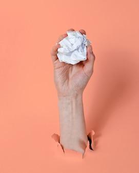 Mano femenina lanza bola de papel arrugado a través del fondo de papel rosa rasgado. concepto de idea minimalista