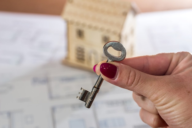 Mano femenina con llave y casa de juguete en plan