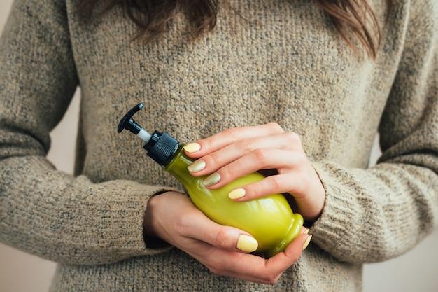 Mano femenina con una manicura amarilla que sostiene la botella verde con crema cosmética