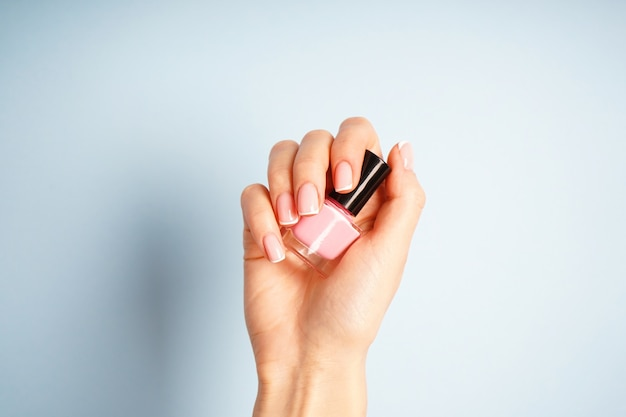 Mano femenina con manicura francesa elegante, sostiene una botella con esmalte de uñas. concepto de spa y manicura.