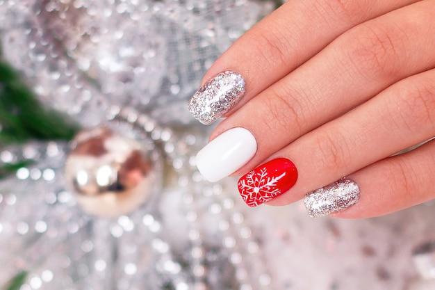 Mano femenina con uñas de manicura de invierno