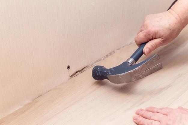 Mano femenina con martillo de metal martillo clavija de plástico en la pared. concepto de reparación del hogar.