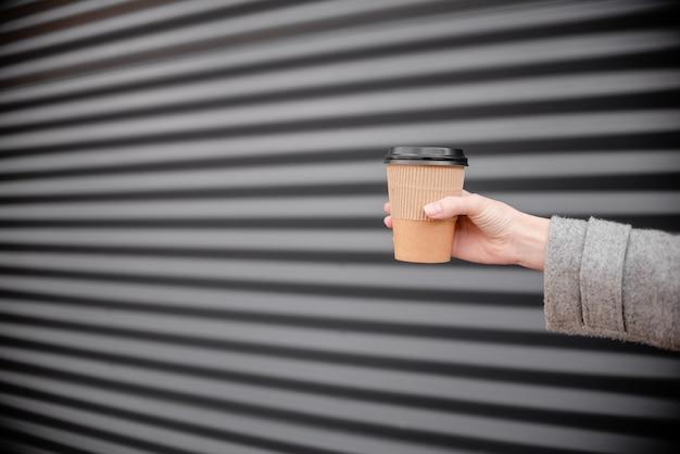 Mano femenina de la mujer con café de la taza de café latte.