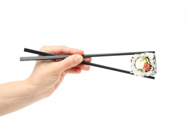 Mano femenina con palillos sostiene sushi roll, aislado en superficie blanca
