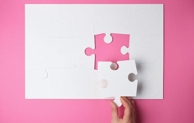 La mano femenina pone grandes rompecabezas blancos en rosa