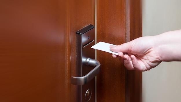 Mano femenina poniendo el interruptor de la tarjeta de llave para abrir la puerta de la habitación del hotel.