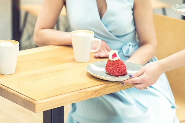 La mano femenina poniendo un pedazo de pastel sobre la mesa