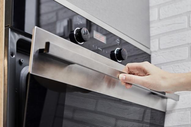 Mano femenina que abre la puerta del horno en la cocina. aparato de cocina abierta en la cocina doméstica. concepto de mejoras para el hogar
