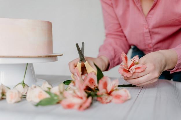 Mano femenina que adorna la torta de cumpleaños rosada de la boda de la flor en soporte.