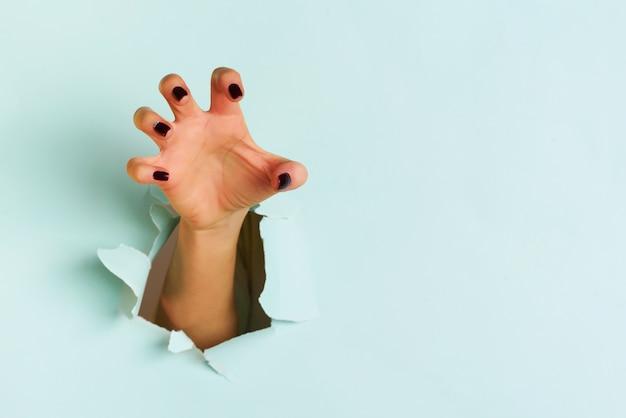 Mano femenina que alcanza a través de la hoja de papel azul rasgada