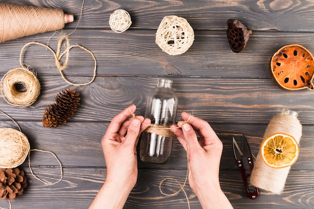 Mano femenina que ata la botella de vidrio con una cuerda cerca del cortador; vaina de loto seca; rodajas de fruta seca; cono de pino sobre superficie de madera con textura