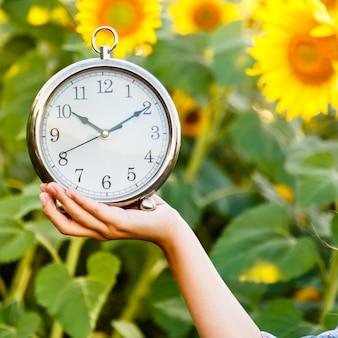 Mano femenina que celebra un reloj en un bacground del campo del girasol. es hora de hacer concepto.