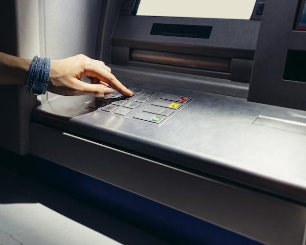 Mano femenina que ingresa el código secreto en el cajero automático por la noche en la calle