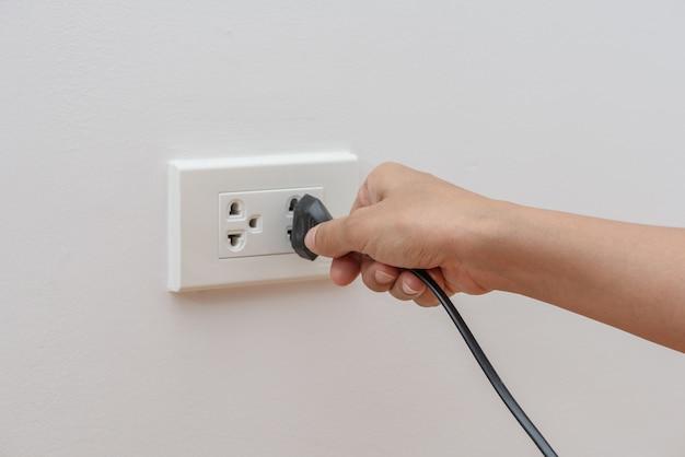 Mano femenina que intenta enchufar el dispositivo al mercado eléctrico en la pared. concepto de ahorro de energía