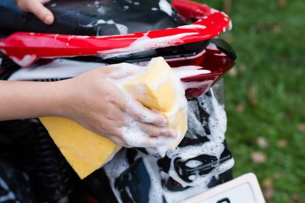 Mano femenina que lava una motocicleta.