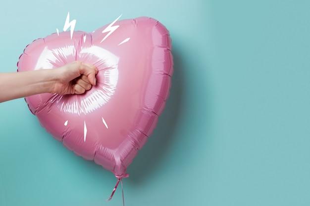 Mano femenina que perfora un globo en forma de corazón