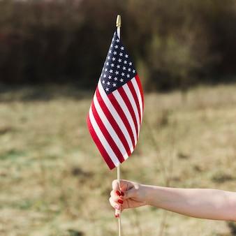 Mano femenina que sostiene la bandera de estados unidos durante el día de la independencia