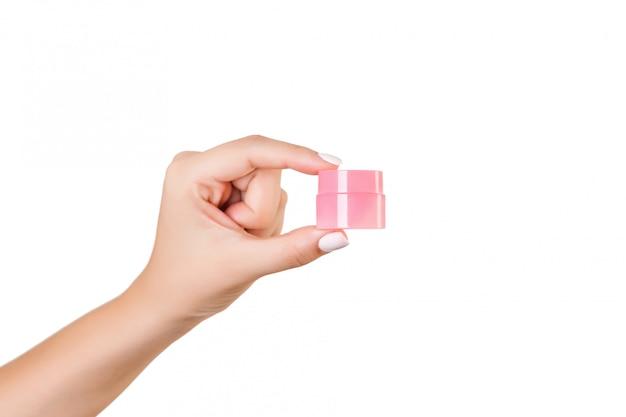 Mano femenina que sostiene la botella de crema de loción aislada