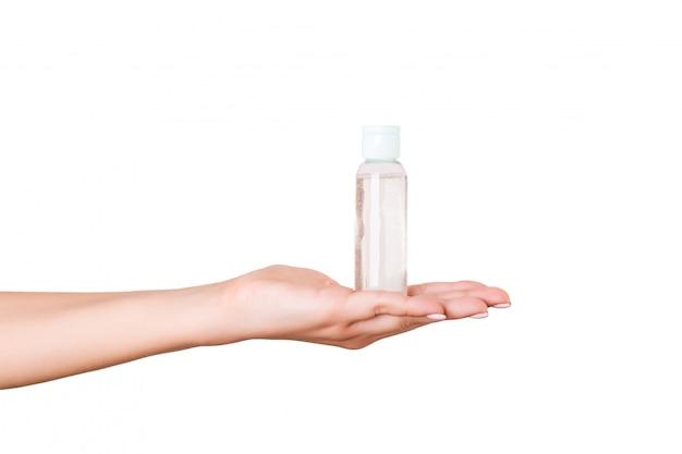 Mano femenina que sostiene la botella de crema de loción