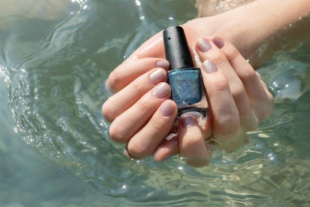 Mano femenina que sostiene la botella púrpura del esmalte de uñas.