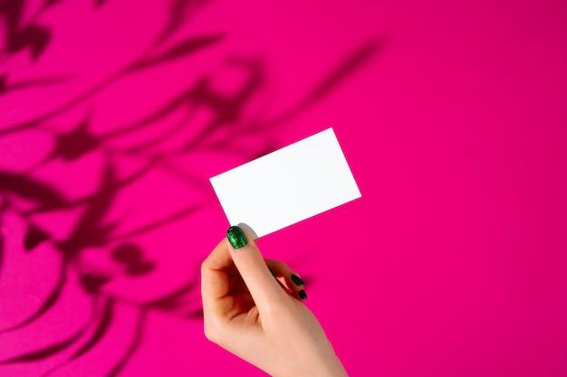 Mano femenina que sostiene businesscard en blanco. foto creativa con sombra