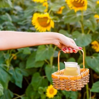 Mano femenina que sostiene una cesta de mimbre con una jarra de aceite de girasol