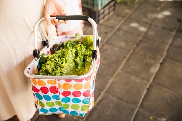 Mano femenina que sostiene la cesta de verduras frescas en mercado