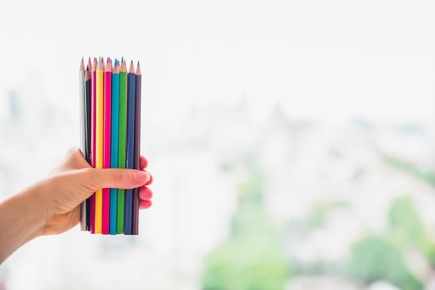 Mano femenina que sostiene el conjunto de lápices de colores contra el fondo borroso