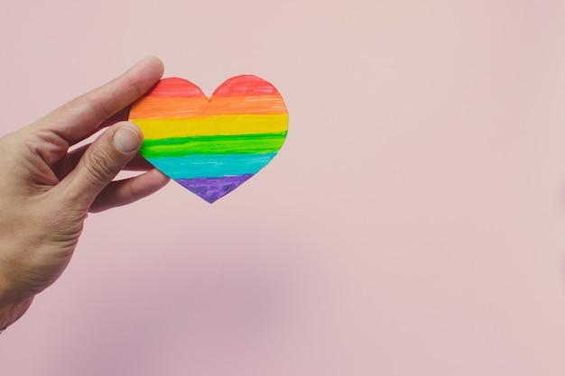 Mano femenina que sostiene el corazón decorativo con rayas de arco iris sobre fondo rosa. bandera del orgullo lgbt, derechos humanos.