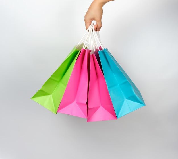 Mano femenina que sostiene cuatro bolsas de embalaje de compras de papel de colores