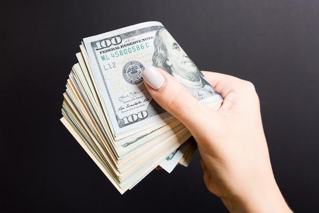 Mano femenina que sostiene firmemente un paquete de dinero. vista superior de cien dólares diferentes. concepto de inversión