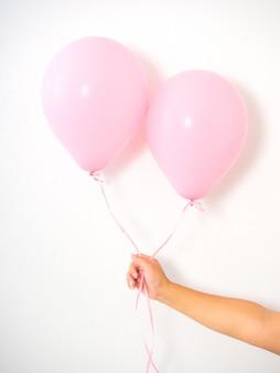 Mano femenina que sostiene los globos rosados