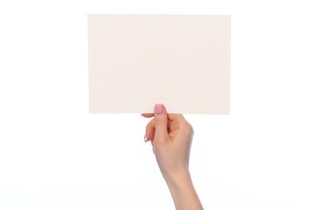Mano femenina que sostiene la hoja de papel blanca en blanco aislada en blanco