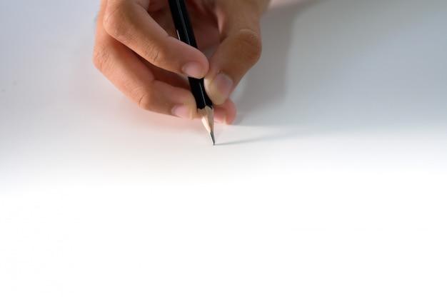 Mano femenina que sostiene el lápiz en la hoja de papel blanco