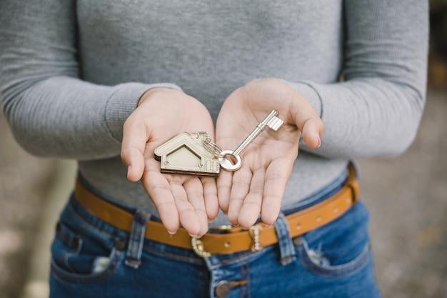 Mano femenina que sostiene la llave de la casa, concepto de agente inmobiliario