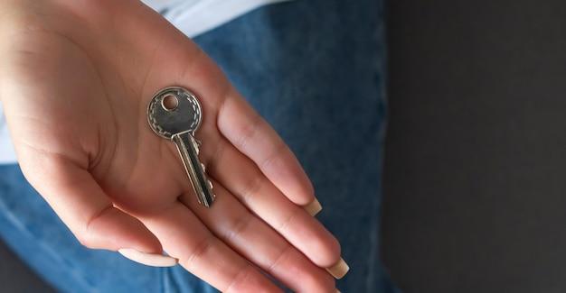 Mano femenina que sostiene el llavero en forma de casa clave.