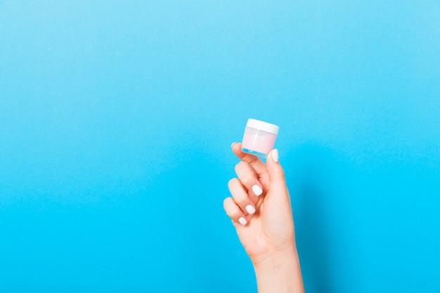 Mano femenina que sostiene la loción poner crema de la botella aislada. chica dar tarro productos cosméticos en azul