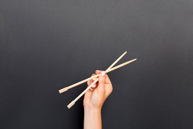 Mano femenina que sostiene los palillos en fondo negro.