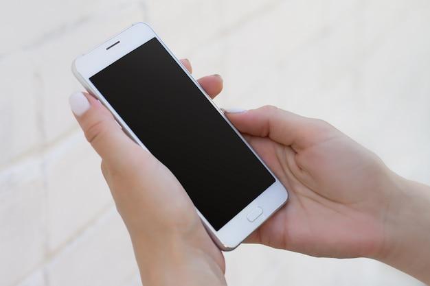 Mano femenina que sostiene smartphone en el fondo blanco de la pared de ladrillo, maqueta con el espacio de la copia