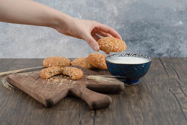Mano femenina que sostiene una sola galleta de avena deliciosa en la superficie de madera.