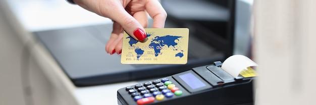 Mano femenina que sostiene la tarjeta bancaria de crédito cerca del primer terminal pos.