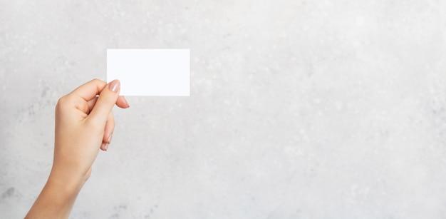 Mano femenina que sostiene una tarjeta de visita en blanco, cortada en fondo concreto gris con el espacio de la copia. plantilla de maqueta de marca.