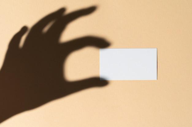 Mano femenina que sostiene la tarjeta de visita en blanco. foto creativa con sombra