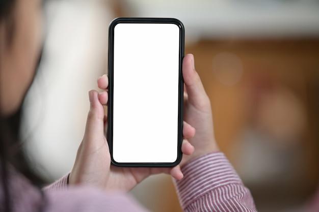 Mano femenina que sostiene el teléfono móvil de pantalla blanca en blanco sobre fondo borroso bokeh